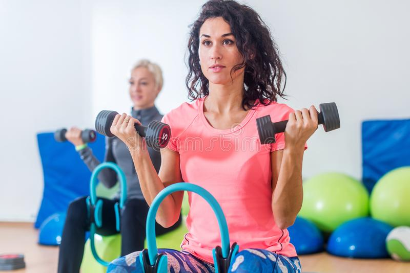 Slanka sportiga kvinnor som utbildar sammantr?de p? ?vningsbollar som rymmer hantlar och pressar den Pilates cirkeln mellan deras arkivfoto