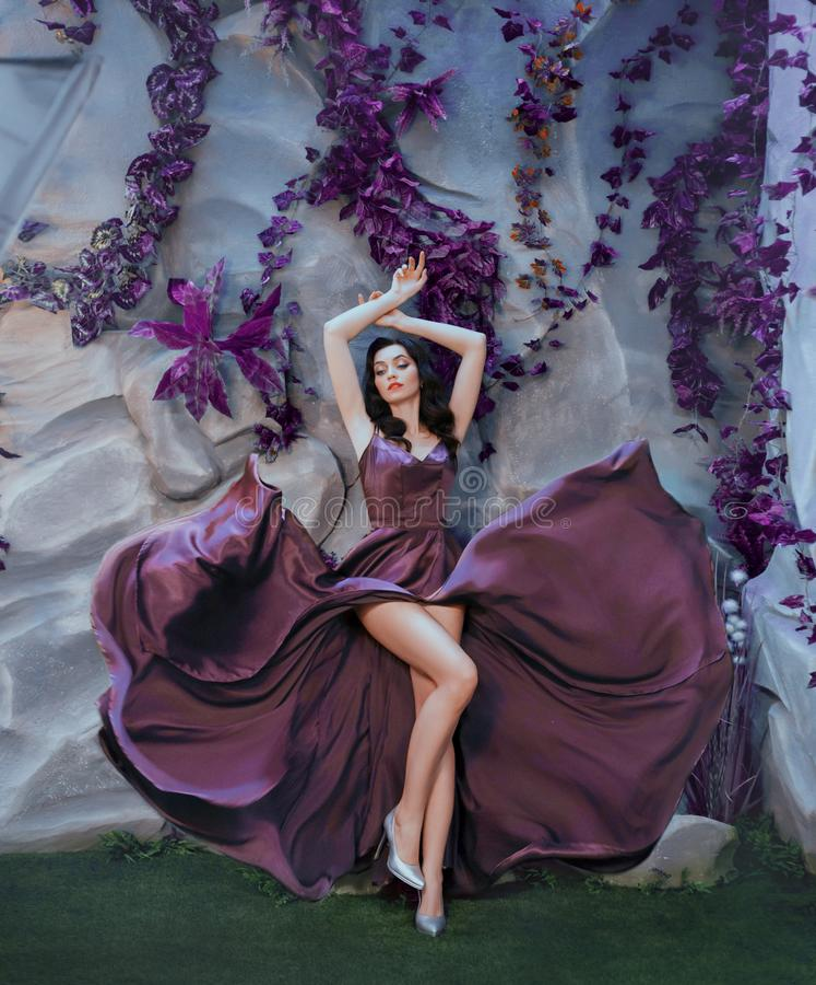 Slanke aantrekkelijke dame zoals beeld van schitterende kunstenaar, vliegende fladderende purpere lange satijnkleding zoals verfs royalty-vrije stock afbeeldingen