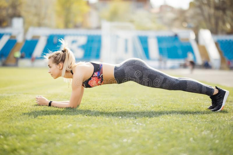 Slanke atletische vrouw die planking oefening in het stadion op groen gras van voetbalgebied doen, sportieve meisjestraining, in  stock foto