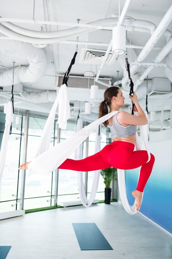 Slanke en actieve vrouw in rode beenkappen die luchtyoga doen stock afbeeldingen