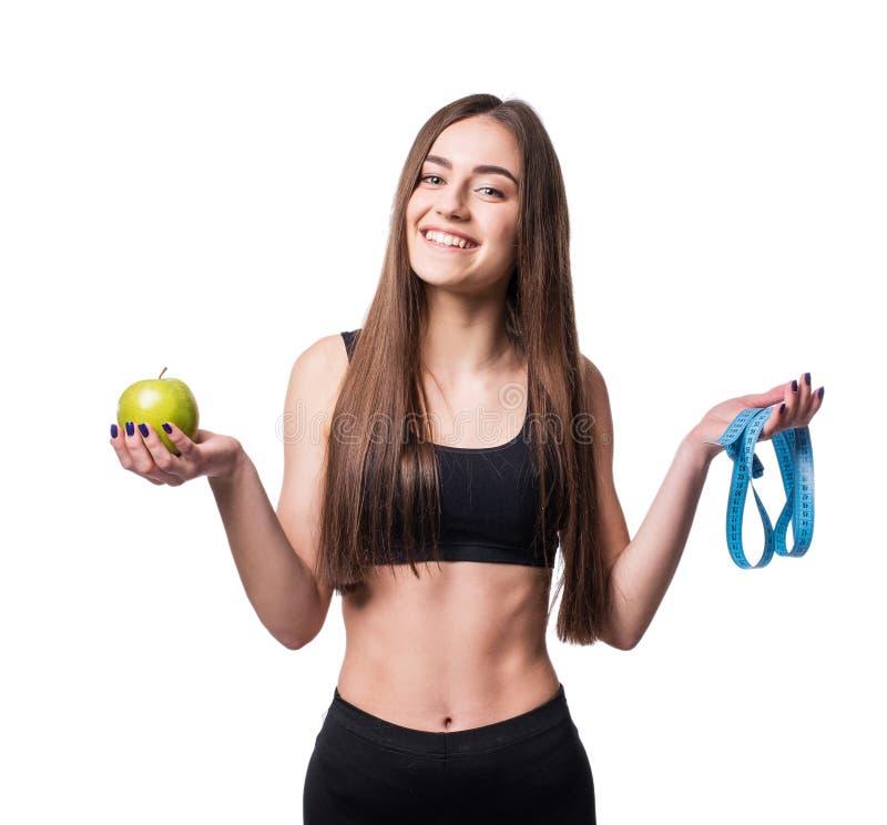 Slanke en gezonde jonge die de maatregelenband en appel van de vrouwenholding op witte achtergrond wordt geïsoleerd Gewichtsverli stock afbeelding