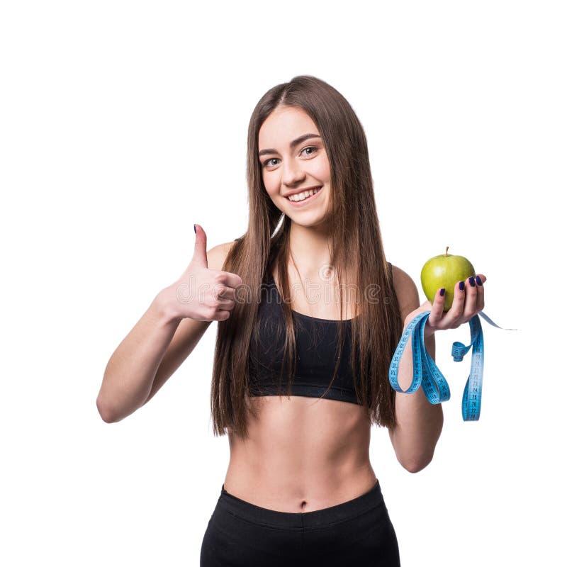 Slanke en gezonde jonge die de maatregelenband en appel van de vrouwenholding op witte achtergrond wordt geïsoleerd Gewichtsverli stock fotografie