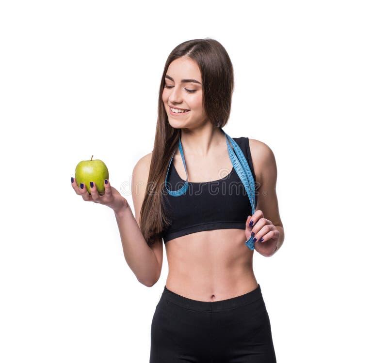 Slanke en gezonde jonge die de maatregelenband en appel van de vrouwenholding op witte achtergrond wordt geïsoleerd Gewichtsverli stock foto's