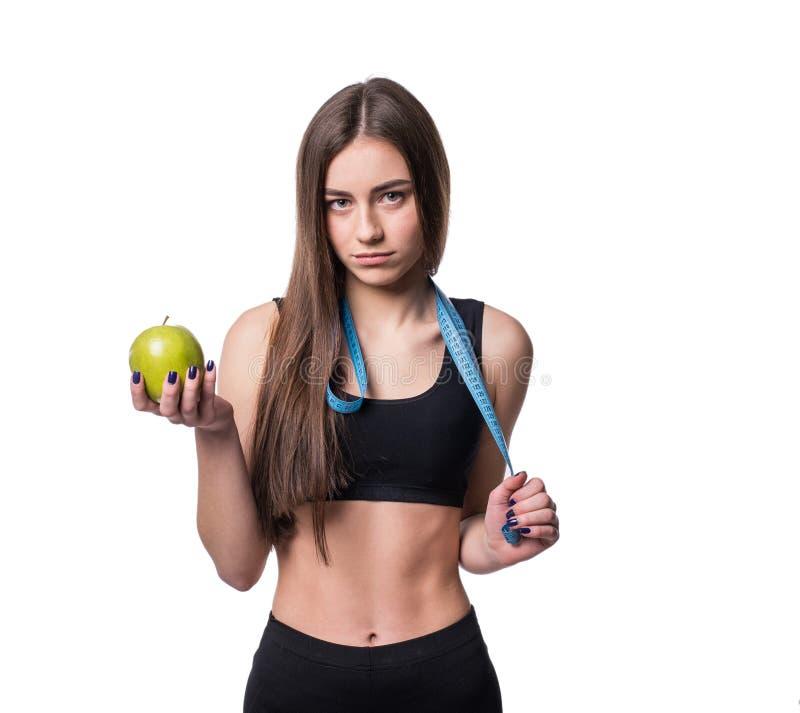 Slanke en gezonde jonge die de maatregelenband en appel van de vrouwenholding op witte achtergrond wordt geïsoleerd Gewichtsverli royalty-vrije stock fotografie