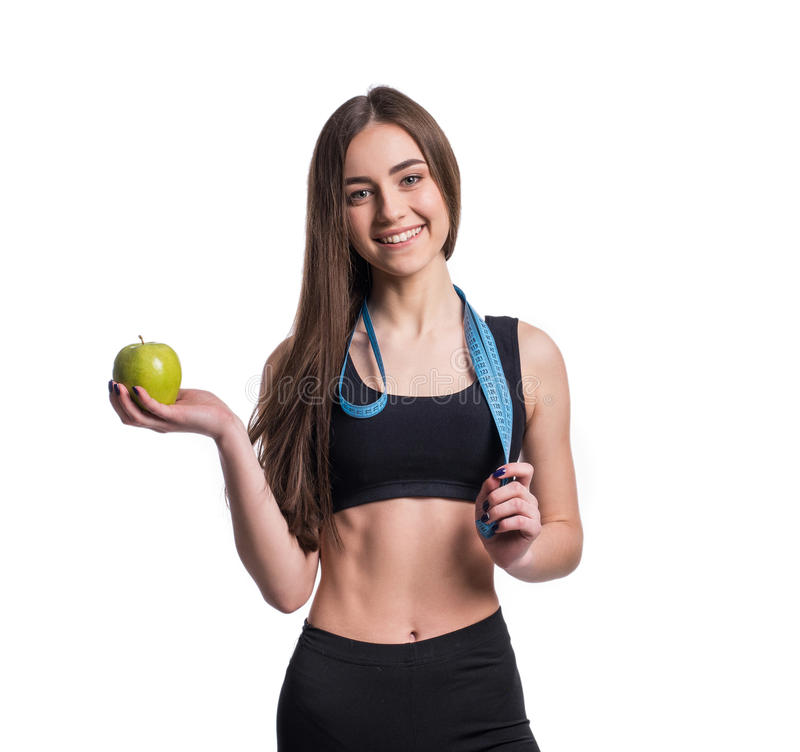 Slanke en gezonde jonge die de maatregelenband en appel van de vrouwenholding op witte achtergrond wordt geïsoleerd Gewichtsverli stock afbeeldingen