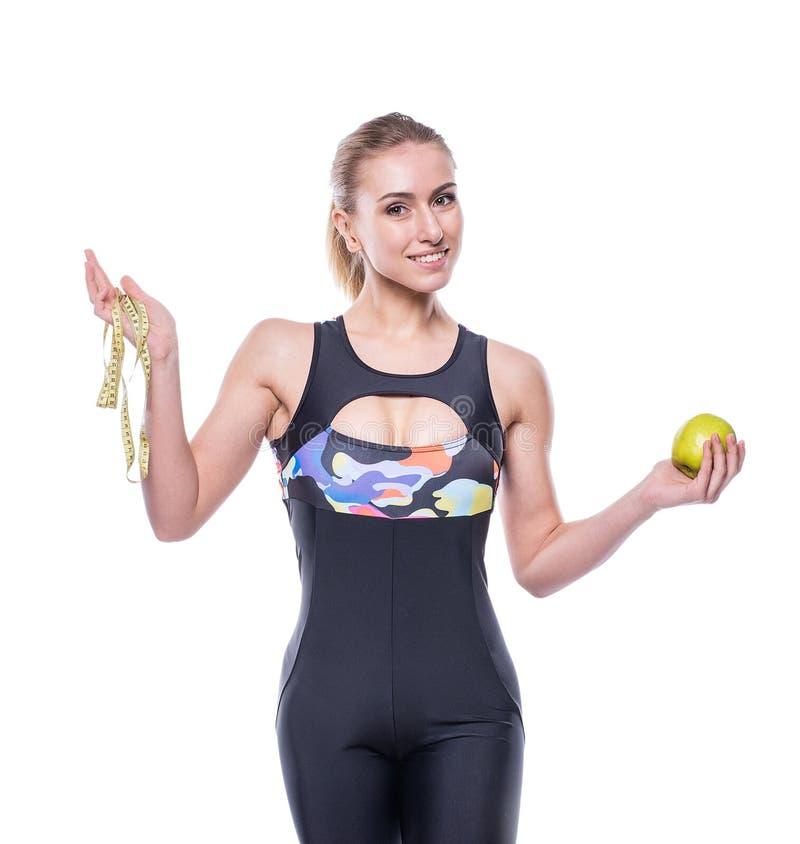 Slanke en gezonde jonge vrouw die de band van de de holdingsmaatregel van de sportkledingsbovenkledij en groene appel dragen die  stock afbeelding