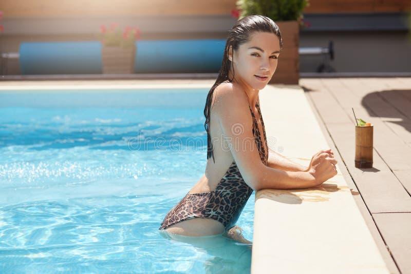 Slanke energieke jonge vrouw die in zwembad blijven, die direct camera bekijken, die onderbreking hebben, zettend wapens op kust, stock fotografie