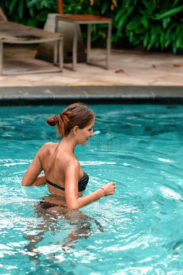 Slanke gelooide vrouw die bij de pool zwemmen Rust en kuuroord Sluit omhoog stock foto