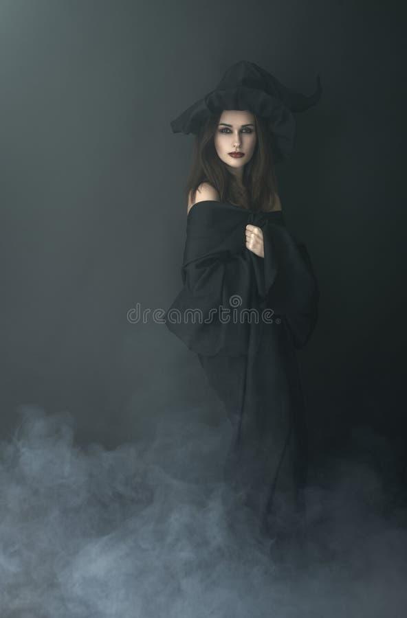 Slanke heks in een rook op zwarte achtergrond stock foto