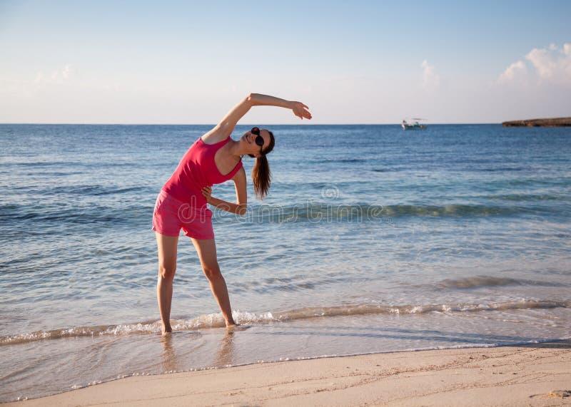 Slanke jonge vrouw die oefeningen op de overzeese kust doen stock foto