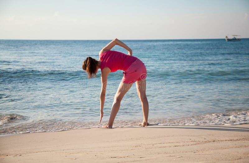 Slanke jonge vrouw die oefeningen op de overzeese kust doen royalty-vrije stock foto