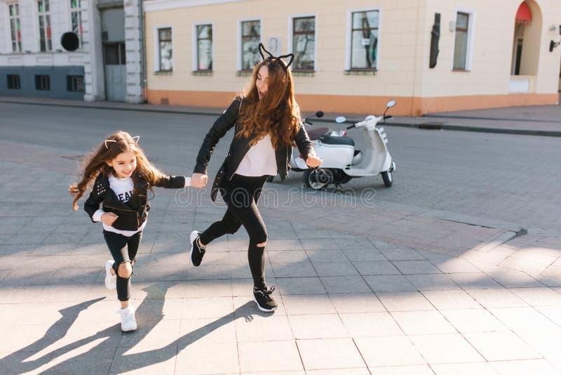 Slanke jonge vrouw in in jeans en leerjasje die de hand van de dochter van de straatholding reduceren Blije langharig royalty-vrije stock fotografie
