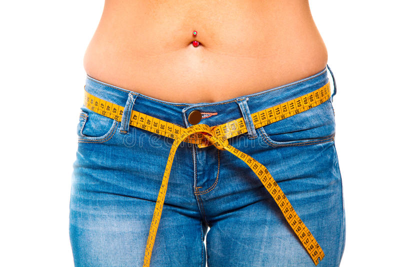 slanke jonge vrouw in jeans met een meetlint na een succe royalty-vrije stock foto's
