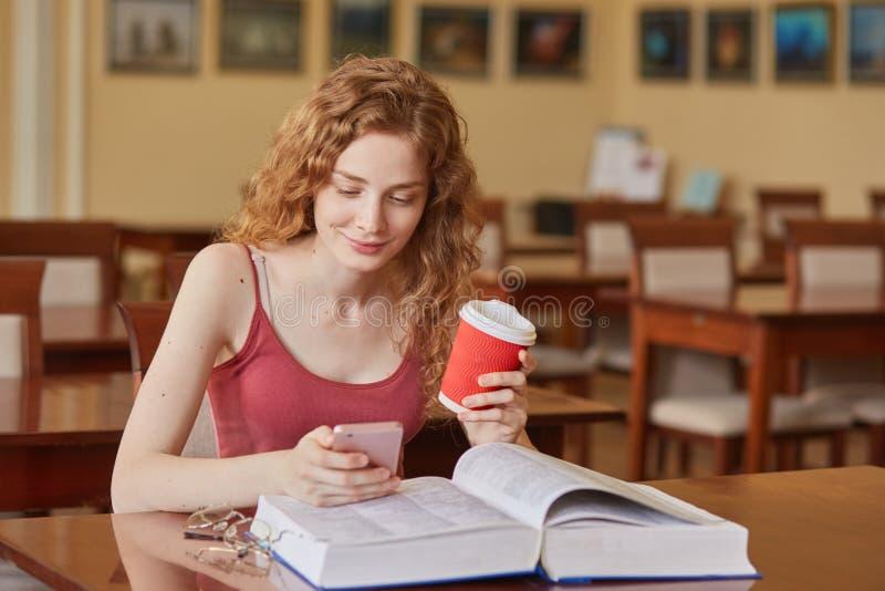 Slanke knappe jonge studentenzitting in lokale bibliotheek, holding papercup van koffie en smartphone, bekijkend het mobiele sche royalty-vrije stock fotografie