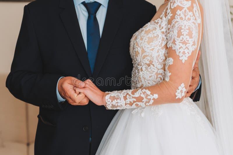 Slanke mooie jonge bruid die de hand van haar vader houden vóór haar huwelijk royalty-vrije stock afbeeldingen