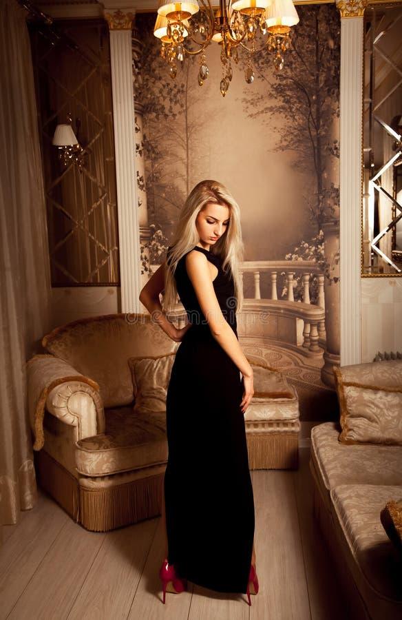 Slanke seksuele blondevrouw in lange zwarte kleding en rode hoge hielen stock fotografie