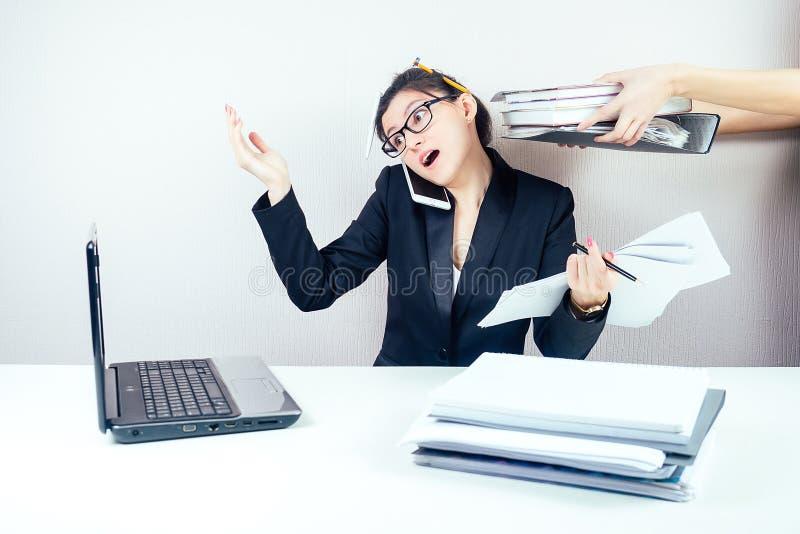 Slanke, slimme, multitasking vrouw zakenvrouw in een stijlvolle werktas en bril die werken met een laptop en stock foto's