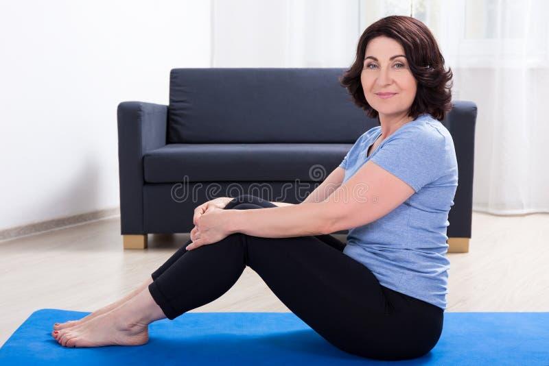 Slanke sportieve rijpe vrouw die oefeningen op yogamat thuis doen royalty-vrije stock afbeelding