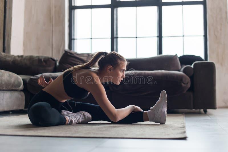 Slanke sportvrouw in de spieren die van de sportkledingsopwarming vóór training uitrekkende oefeningszitting op vloer thuis doen royalty-vrije stock afbeeldingen