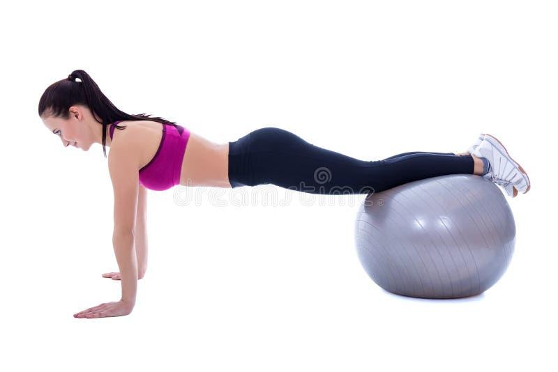 Slanke vrouw die in sportenslijtage duw op oefeningen op fitness bal doen stock afbeeldingen