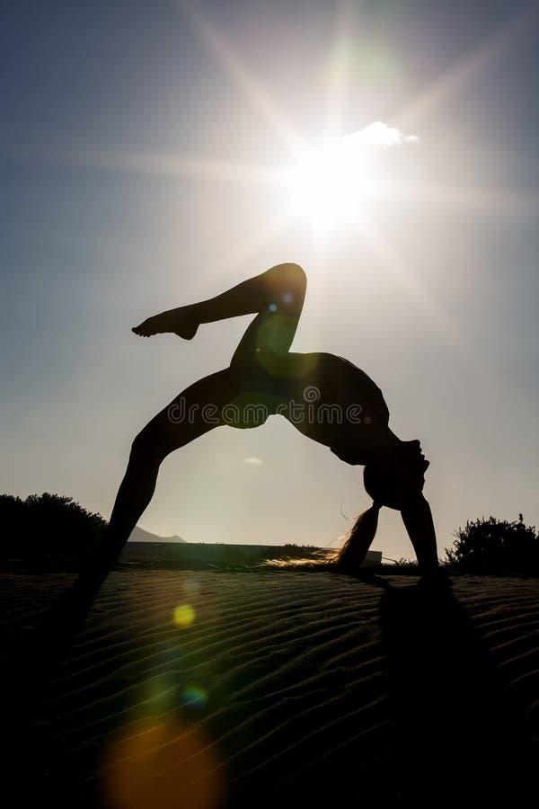 Slanke vrouw die yogapraktijk op strand doen royalty-vrije stock fotografie