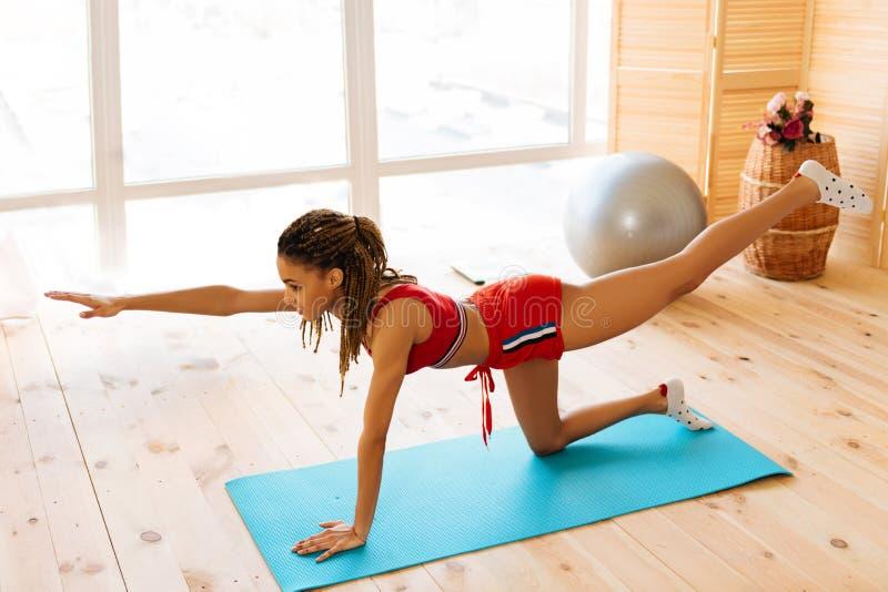 Slanke vrouw rode borrels dragen en bovenkant die ochtend van yoga genieten stock afbeeldingen