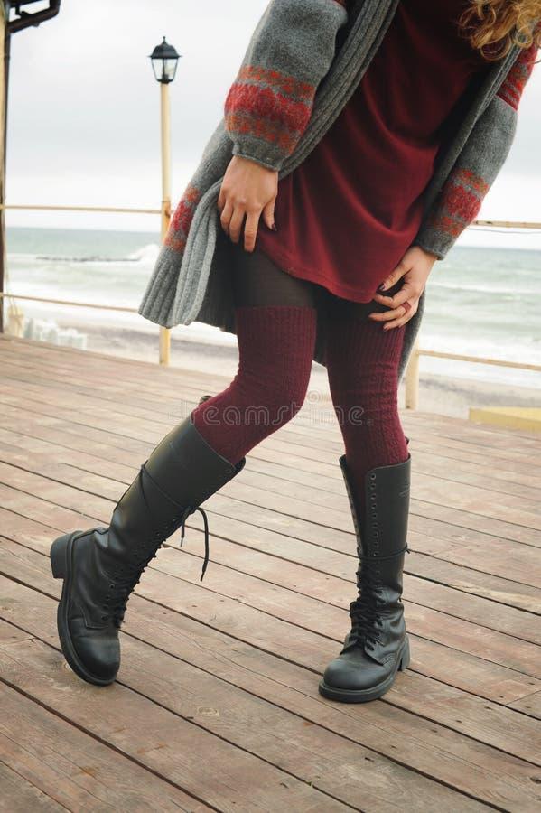 Slanke vrouwelijke benen gekleed in knie hoge laarzen met schoenveters en gebreide kousen stock foto