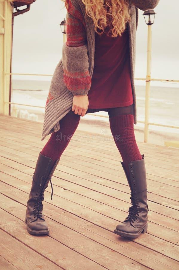 Slanke vrouwelijke benen gekleed in leerschoenen met kant en gebreide stock afbeeldingen