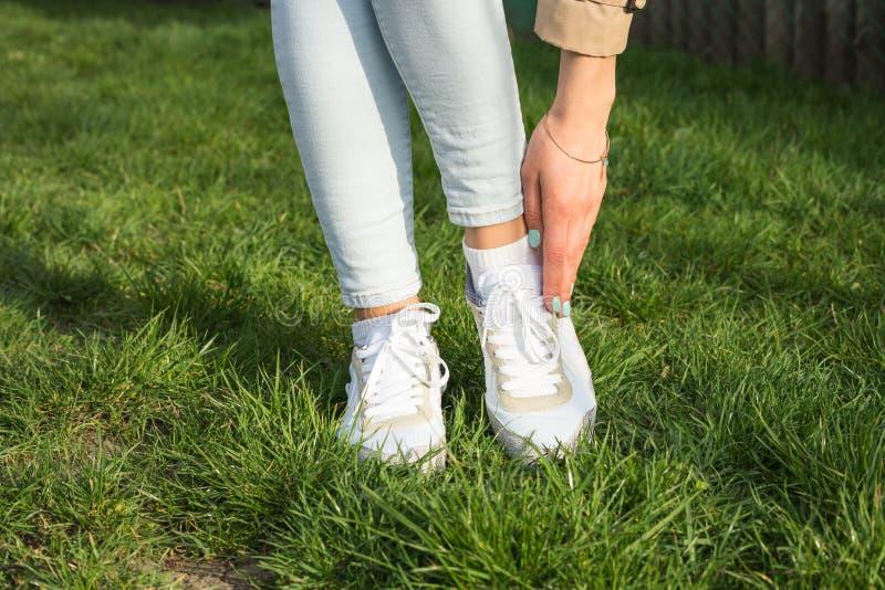 Slanke vrouwelijke benen in jeans en witte tennisschoenen op een groen gazon stock afbeelding
