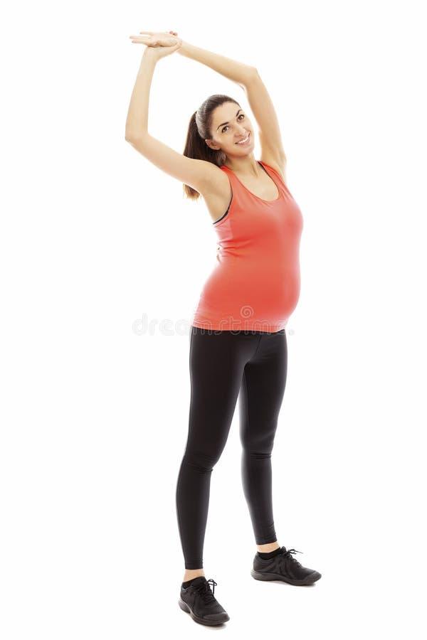 Slanke zwangere vrouw belast met lichamelijke opvoeding, de volledige groei Ge?soleerdj op witte achtergrond royalty-vrije stock foto's