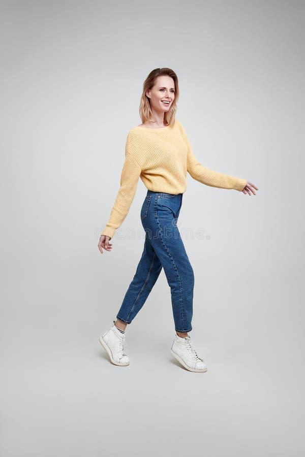 Slankt och h?rligt Fullt längdstudioskott av den attraktiva unga kvinnan i tillfälliga kläder som håller handen på luften och ler royaltyfri fotografi