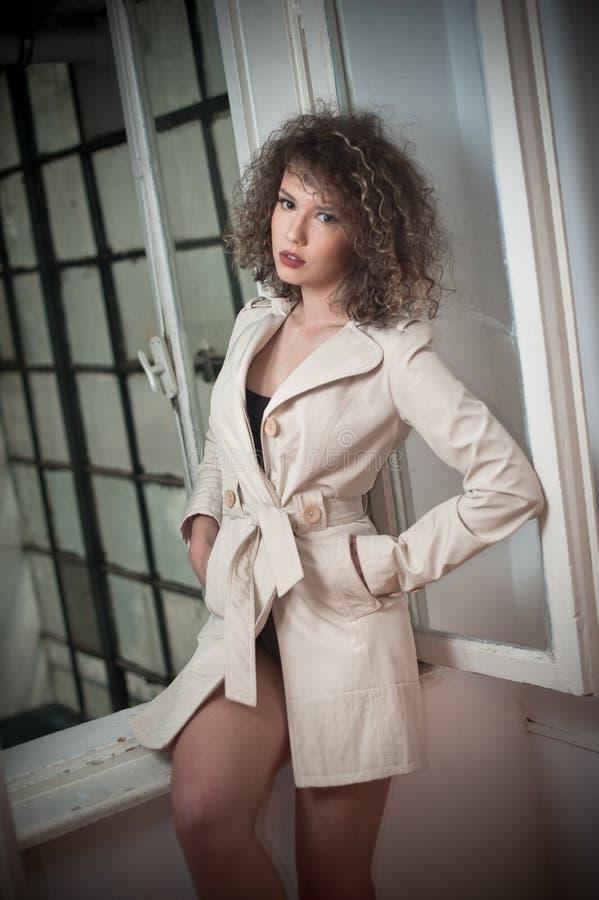Slankt ungt bärande vitt lag för modemodell i fönsterram Älskvärd sexig trendig kvinna med ljus - brunt lockigt hår fotografering för bildbyråer