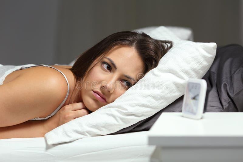 Slapeloos slapeloosheidsmeisje die wekker in de nacht bekijken stock fotografie