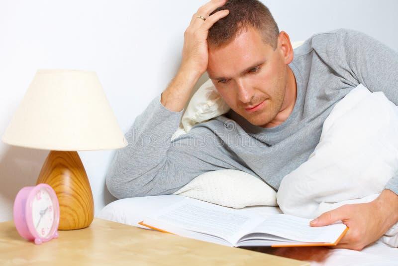 Slapelooze mens die een boek leest stock fotografie