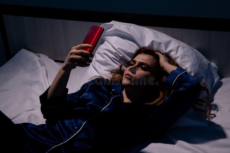 Slapeloze knappe dame die in het bed met telefoon bij nacht liggen stock afbeeldingen