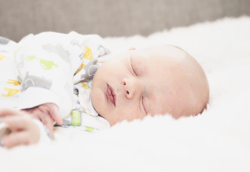Slapen Pasgeboren in Comfortabele Dwarsbalkpyjama's op een Zacht Wit royalty-vrije stock afbeeldingen