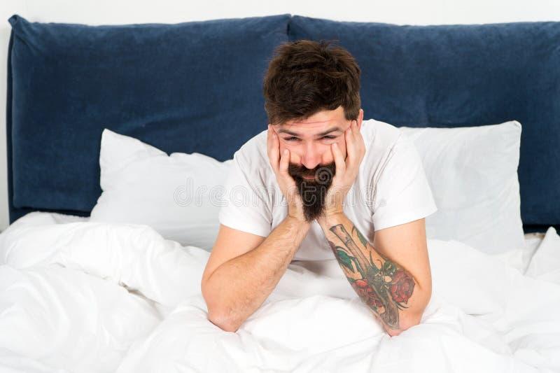 Slaperig het voelen rijp mannetje met baard in pyjama op bed in slaap en wakker energie en vermoeidheid Gebaarde mens hipster royalty-vrije stock afbeeldingen