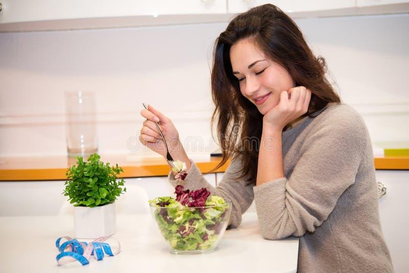 Slaperig meisje met een kom salade in de keuken stock fotografie
