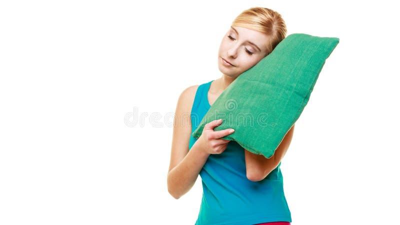 Slaperig vermoeid blondemeisje met groen hoofdkussen stock fotografie