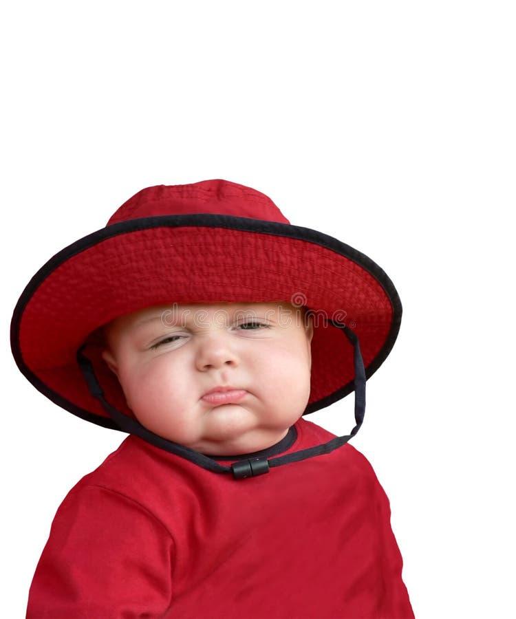 Slaperige baby in rode hoed. stock fotografie
