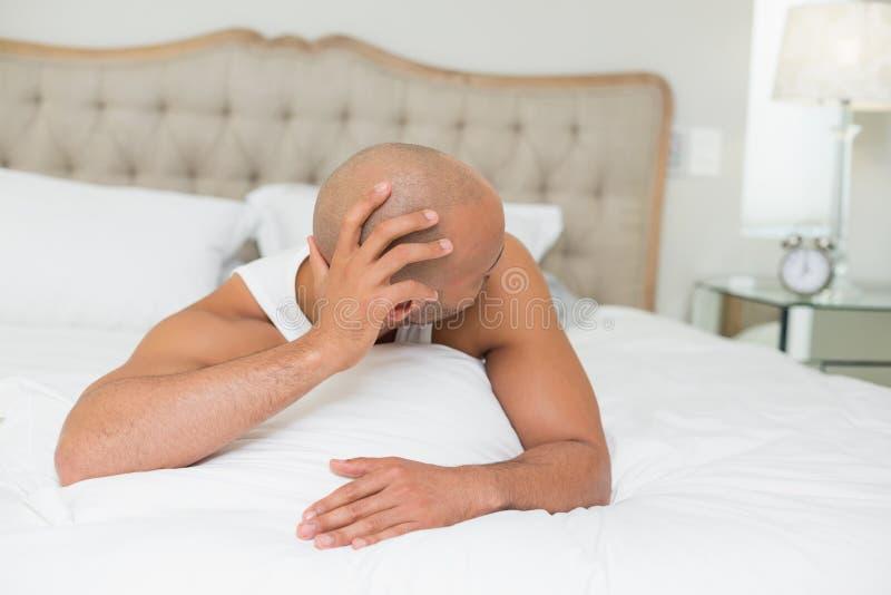 Slaperige kale mens die wekker in bed bekijken royalty-vrije stock fotografie