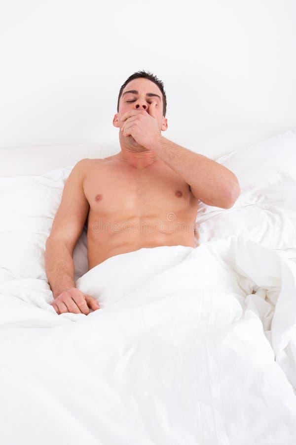Slaperige mens die in bed thuis ontwaken geeuwen royalty-vrije stock foto