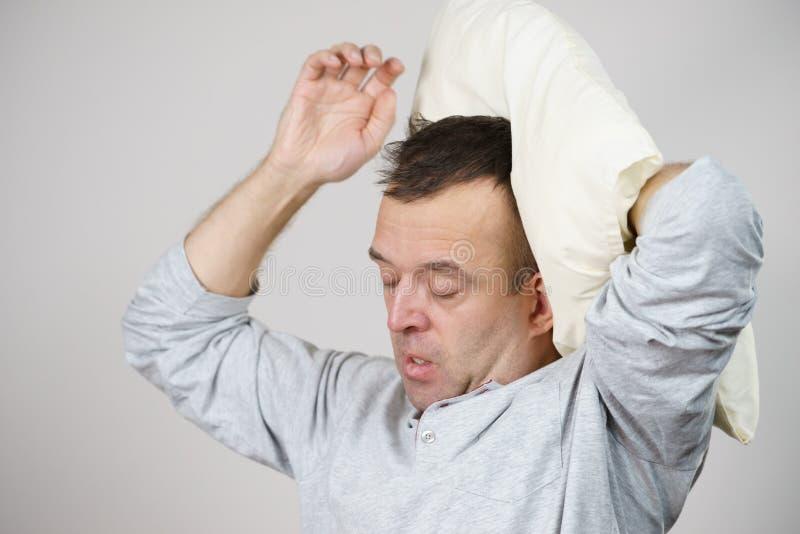 Slaperige mens vermoeid met hoofdkussen op grijs royalty-vrije stock foto's