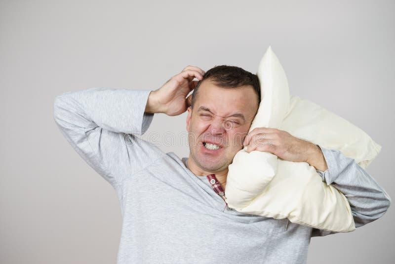 Slaperige mens vermoeid met hoofdkussen op grijs stock foto