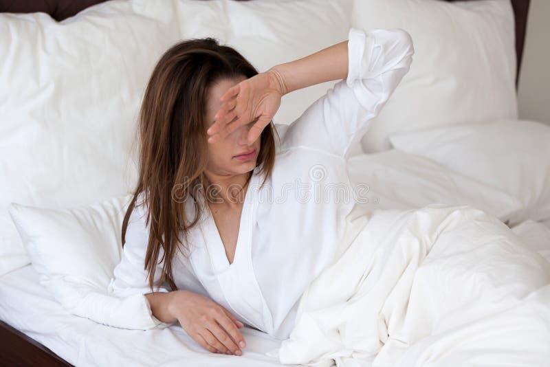 Slaperige millennial vrouw die aan slechte slaapontwaken lijden royalty-vrije stock afbeelding