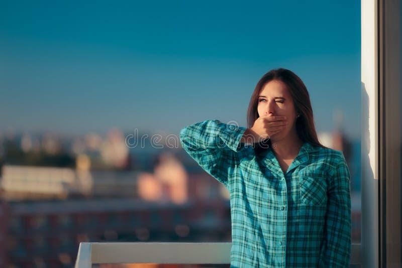 Slaperige ochtendvrouw die in pyjama's in het balkon geeuwen royalty-vrije stock foto