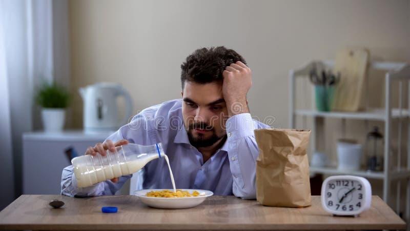Slaperige overwerkte vrijgezel die cornflakes met melk in ochtend, moeheid eten stock afbeeldingen