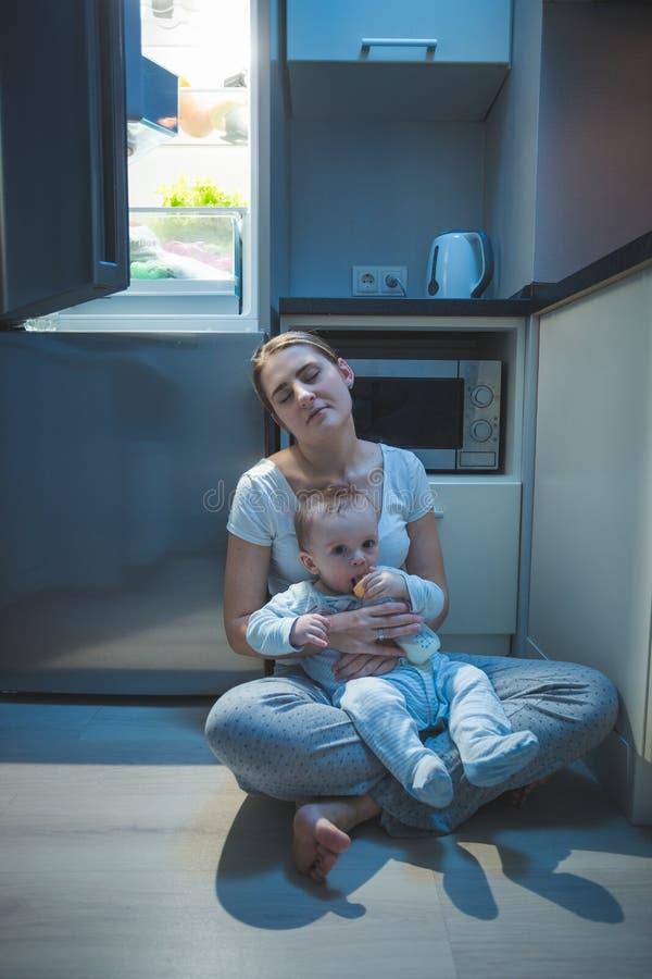 Slaperige vermoeide de keukenvloer van de vrouwenzitting bij nacht en het voeden van haar babyjongen met melk stock fotografie