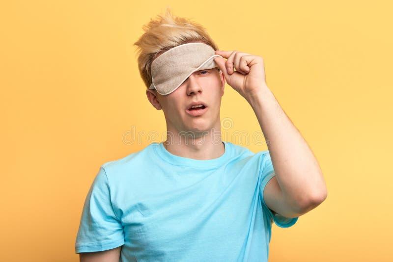 Slaperige vermoeide uitgeputte mens die het slaapmasker opstijgen royalty-vrije stock fotografie