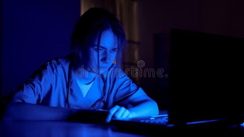 Slaperige verpleegster op plichtszitting in donkere ruimte, uitgeput door het extra werk in het ziekenhuis stock foto's